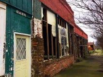 Запертая желтая дверь на зданиях около забытого тротуара стоковая фотография rf