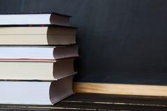 записывает старую принципиальной схемы изолированная образованием Стог книг с доской в предпосылке Стоковые Изображения RF