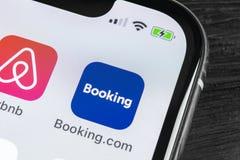 записывая значок применения com на конце-вверх экрана iPhone x Яблока Значок app резервирования записывая com Социальные средства стоковые фотографии rf