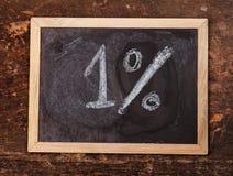 Запись 1% на классн классном с белым мелом на деревянной предпосылке Стоковое Изображение