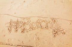 Запись на песке пляжа среди следов ноги Стоковая Фотография