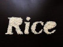 Запись риса слова с семенами риса на таблице с коричневой деревянной предпосылкой стоковые фото