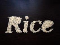 Запись риса слова с семенами риса на таблице с коричневой деревянной предпосылкой стоковые изображения rf