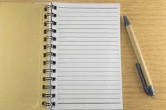 Запишите с ручкой на деревянном поле Стоковые Фото