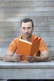запишите человека outdoors читая детенышей Стоковые Изображения RF