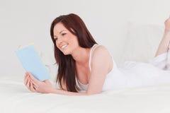 запишите шикарную с волосами женщину красного цвета чтения стоковое фото rf