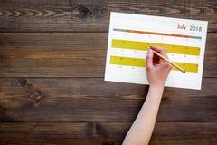 запланирование Укажите дата в календаре карандашем Установите цель Выберите дату Календарь на темном деревянном взгляд сверху пре стоковое фото rf