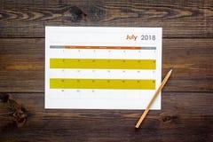 запланирование Укажите дата в календаре карандашем Установите цель Выберите дату Календарь на темном деревянном взгляд сверху пре стоковое изображение