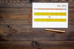 запланирование Укажите дата в календаре pushpin Установите цель Выберите дату Календарь на темном деревянном взгляд сверху предпо стоковое фото