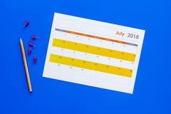 запланирование Укажите дата в календаре pushpin Установите цель Выберите дату Календарь на голубом взгляд сверху предпосылки стоковая фотография