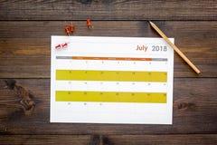 запланирование Укажите дата в календаре pushpin Установите цель Выберите дату Календарь на темном деревянном взгляд сверху предпо стоковое фото rf