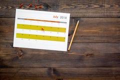 запланирование Укажите дата в календаре pushpin Установите цель Выберите дату Календарь на темном деревянном взгляд сверху предпо стоковые фото