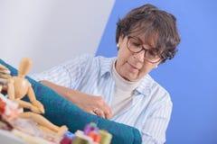 Заплатка зрелой женщины брюнет шить Стоковая Фотография RF