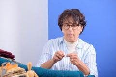 Заплатка зрелой женщины брюнет шить Стоковое фото RF