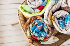 Заплатка и концепция моды - крупный план на 3 красивых лоскутных одеялах свернул в трубку и клал в плетеный стул Стоковые Фотографии RF