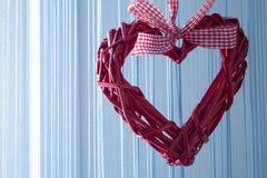 Заплетенное красное сердце на голубой предпосылке стоковое изображение rf