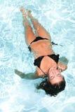 заплывание девушки красоты в бассейне в доме курортного отеля стоковые изображения