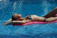 Заплывание женщины на тюфяке воздуха стоковые изображения rf