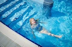 Заплывание маленького ребенка в бассейне стоковое изображение