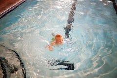 Заплывание маленького ребенка в крытом бассейне на гостинице стоковая фотография rf