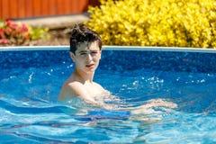 Заплывание мальчика в бассеине стоковые фотографии rf