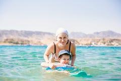 Заплывание матери и младенца с раздувным кольцом в море праздник призвание стоковое изображение rf