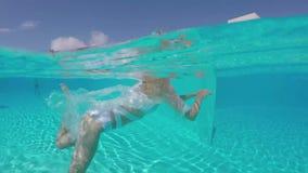 Заплывание молодой женщины красоты под водой в открытом бассейне видеоматериал