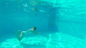 Заплывание молодой женщины красоты под водой в открытом бассейне акции видеоматериалы