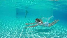 Заплывание молодой женщины красоты под водой в открытом бассейне сток-видео