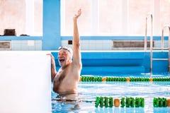 Заплывание старшего человека в крытом бассейне стоковая фотография
