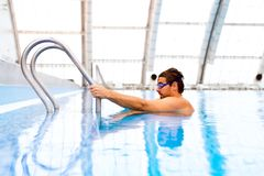 Заплывание человека в крытом бассейне Стоковое Изображение RF