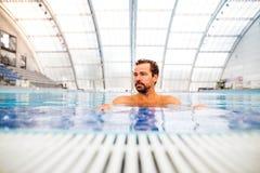 Заплывание человека в крытом бассейне Стоковые Фотографии RF