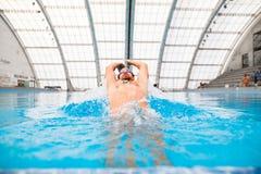 Заплывание человека в крытом бассейне Стоковое Изображение