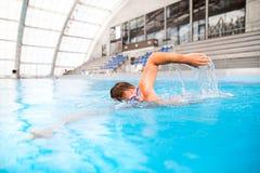 Заплывание человека в крытом бассейне Стоковое Фото