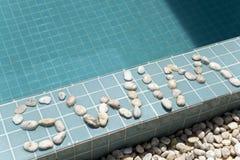 ` Заплыва ` надписи положено вне камешком на сторону бассейна стоковое фото rf