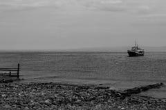 Заплывы корабля к берегу Стоковая Фотография
