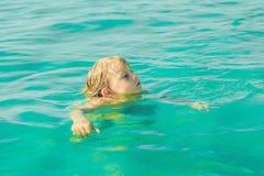 Заплывы мальчика в голубом тропическом море горячее лето стоковое фото rf