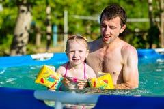 Заплыв отца и дочери в бассейне Заплывы девушки в подушках Стоковое Изображение RF