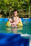 Заплыв отца и дочери в бассейне Заплывы девушки в подушках Стоковое Изображение