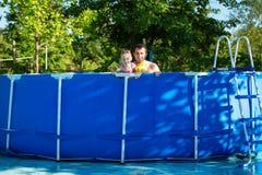 Заплыв отца и дочери в бассейне Заплывы девушки в подушках Стоковое Фото