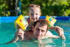 Заплыв отца и дочери в бассейне Катание девушки на человеке Она плавает в подушках Стоковая Фотография RF