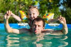 Заплыв отца и дочери в бассейне Катание девушки на человеке Она плавает в подушках Стоковые Изображения