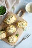 Заполненные половины картошки с цыпленком, соленьями и сыром стоковые изображения