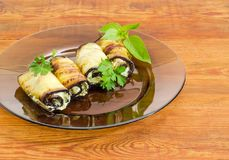 Заполненный баклажан свертывает на стеклянном блюде на деревянной поверхности Стоковое Изображение RF