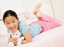 заполненный класть животной девушки кровати счастливый Стоковая Фотография RF
