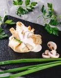 Заполненный крепирует покрытый с соусом и зелеными цветами julienne гриба в плите над темной серой каменной поверхностью Неделя и стоковое фото rf
