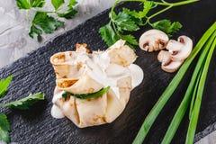 Заполненный крепирует покрытый с соусом и зелеными цветами julienne гриба в плите над темной серой каменной поверхностью Неделя и стоковое изображение