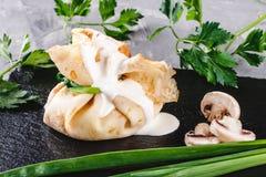 Заполненный крепирует покрытый с соусом и зелеными цветами julienne гриба в плите над темной серой каменной поверхностью Неделя и стоковое фото