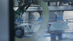 Заполняя бутылки с питьевой водой на конвейерной ленте в мастерской компании видеоматериал