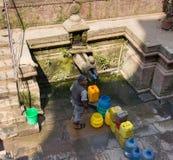 Заполняя ведра воды в Катманду, Непале стоковые изображения